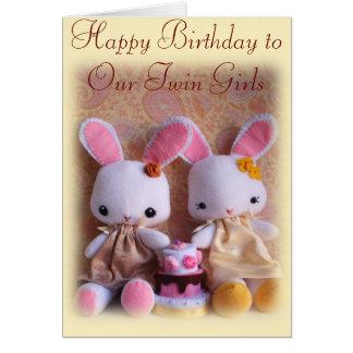 Conejitos gemelos con la tarjeta del feliz