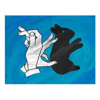 Conejo de la sombra en azul postal