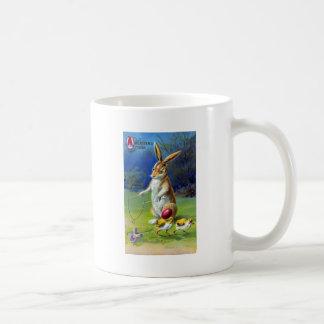 Conejo de Pascua que juega al juego con los pollue Taza