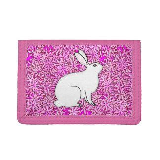 Conejo en una cama de las flores de la primavera