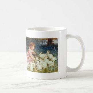 Conejos de alimentación del chica taza de café