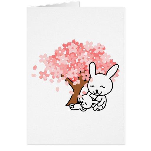 Conejos de conejito felices debajo de un cerezo tarjeton