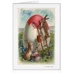 Conejos que pintan un huevo tarjeta de felicitación