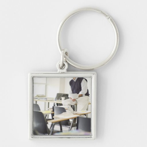 Confident professor leaning on desk in classroom keychain