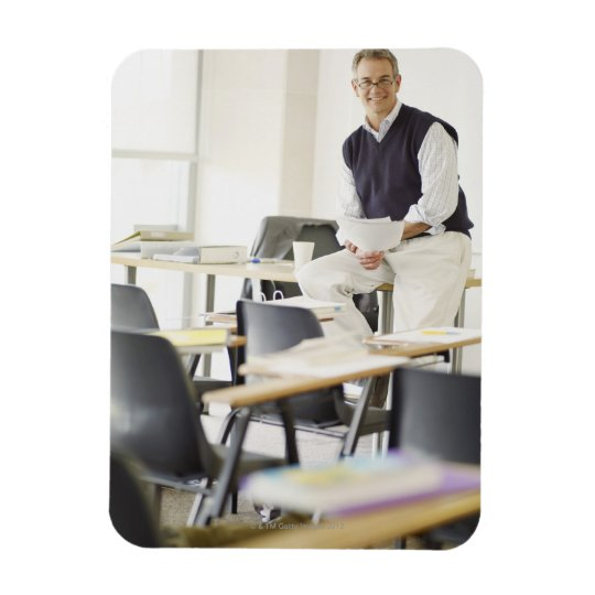 Confident professor leaning on desk in classroom magnet
