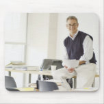 Confident professor leaning on desk in classroom mouse pad