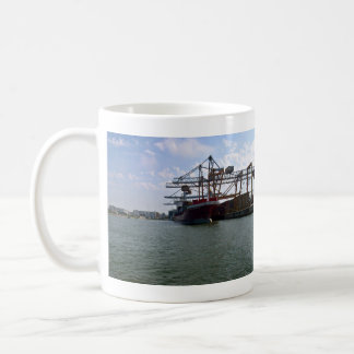 Container ships stacked in port against blue sky coffee mug