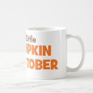 Contando con una pequeña calabaza en octubre taza de café