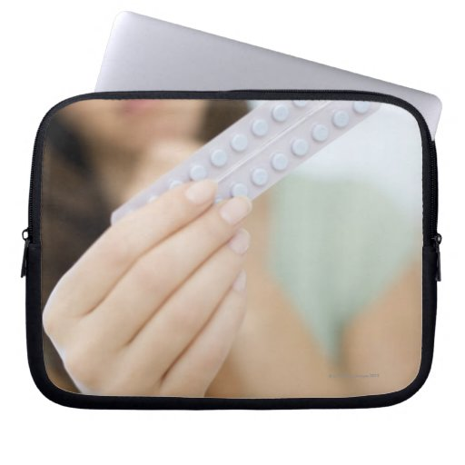 Contraceptive pills in a woman's hand. laptop computer sleeve