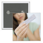 Contraceptive pills in a woman's hand. pinback button