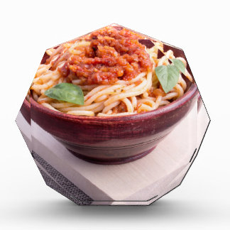 Cooked spaghetti in a brown small wooden bowl award