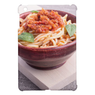 Cooked spaghetti in a brown small wooden bowl case for the iPad mini