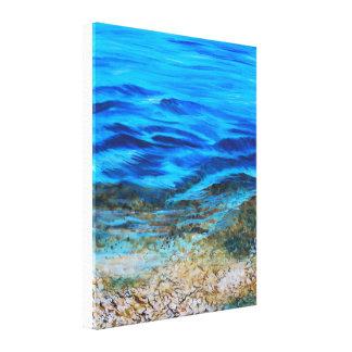cool lake water greeting a rocky beach canvas print