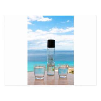 Cool water filled bottle and glasses postcard