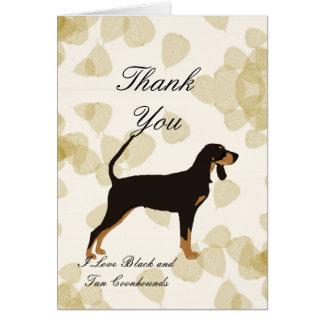 Coonhound negro y del moreno en las hojas del tarjeta pequeña
