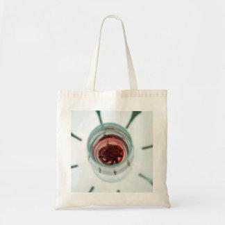 Copa de vino con los pétalos de la flor dentro bolsa de mano