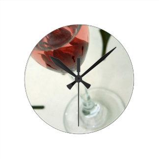 Copa de vino con los pétalos de la flor dentro reloj de pared