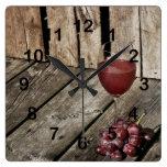 Copa de vino y uvas rojas en la textura de madera relojes