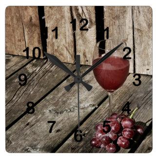 Copa de vino y uvas rojas en la textura de madera reloj cuadrado