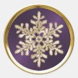 Copo de nieve cristalino del oro en el sello del pegatina redonda
