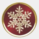 Copo de nieve cristalino del oro en el sello rojo etiqueta