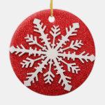 Copo de nieve rojo en un fondo rojo del brillo ornamento de reyes magos