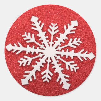 Copo de nieve rojo en un fondo rojo del brillo pegatina redonda