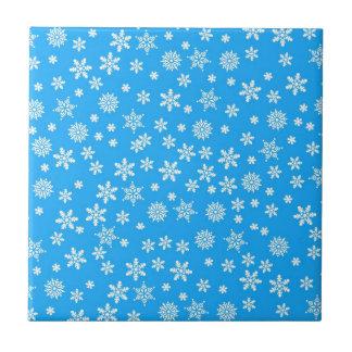 Copos de nieve blancos en fondo azul claro tejas