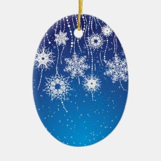 Copos de nieve que cuelgan chispeantes en azul adorno ovalado de cerámica