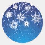 Copos de nieve que cuelgan chispeantes en azul pegatina redonda