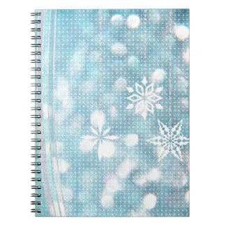 Copos de nieve y cintas en luces verdes de la libro de apuntes