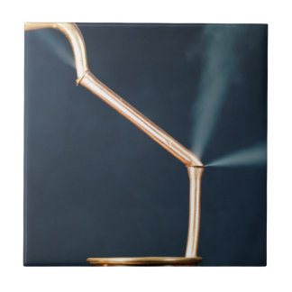 Copper pipes with a leak and steam. ceramic tile