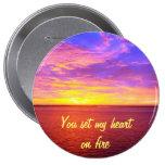 Corazón ardiente de la puesta del sol en el botón  pin