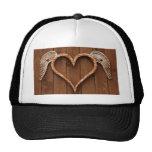 Corazón con las alas contra los tableros de madera gorros