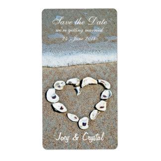 Corazón de cáscaras en la reserva de la playa la e etiquetas de envío