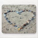 Corazón de piedra en arena tapete de ratón