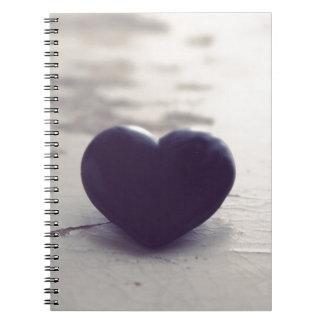 Corazón de piedra púrpura solo en una playa de spiral notebook