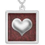 Corazón de plata hinchado en el collar rojo
