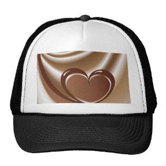 Corazón del chocolate de una cinta en el fondo de gorra