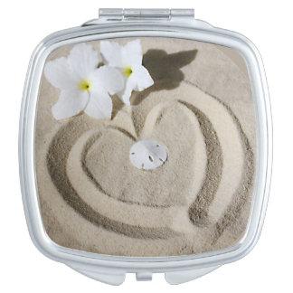 Corazón dibujado en arena con las flores blancas espejo maquillaje