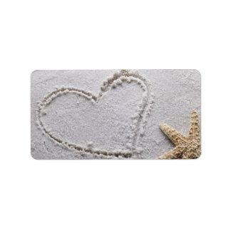 Corazón dibujado en arena en la plantilla de las e etiqueta de dirección