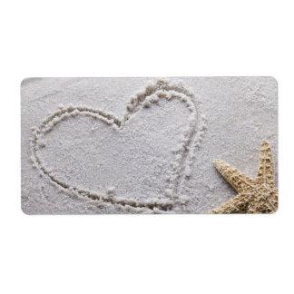 Corazón dibujado en arena en la plantilla de las e etiqueta de envío