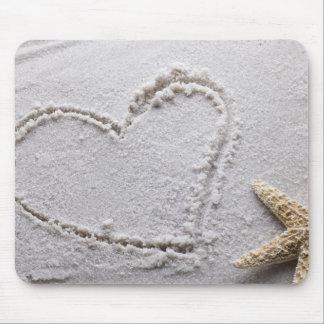Corazón dibujado en arena en la plantilla de las e alfombrilla de ratones
