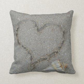 corazón en la arena con la cáscara cojines