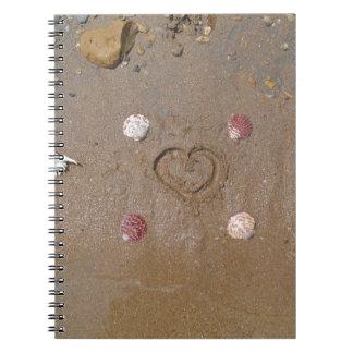 corazón en la arena con las cáscaras libros de apuntes con espiral
