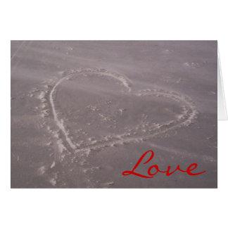 Corazón en la tarjeta del amor de la arena