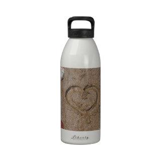 corazón en las cáscaras del rosa de la playa botellas de beber