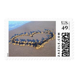 Corazón en los sellos del amor de la arena