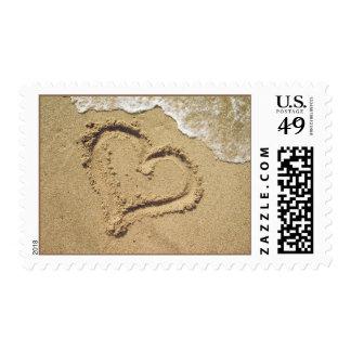Corazón en sellos del amor de la arena
