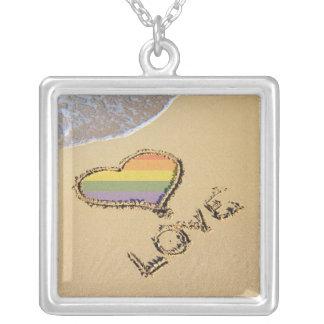 Corazón gay del amor del arco iris en la arena colgante cuadrado